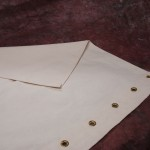 Apron with grommets and hemmed edges